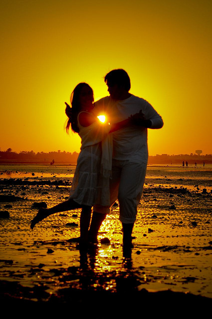 couple dancing on the beach at sunset