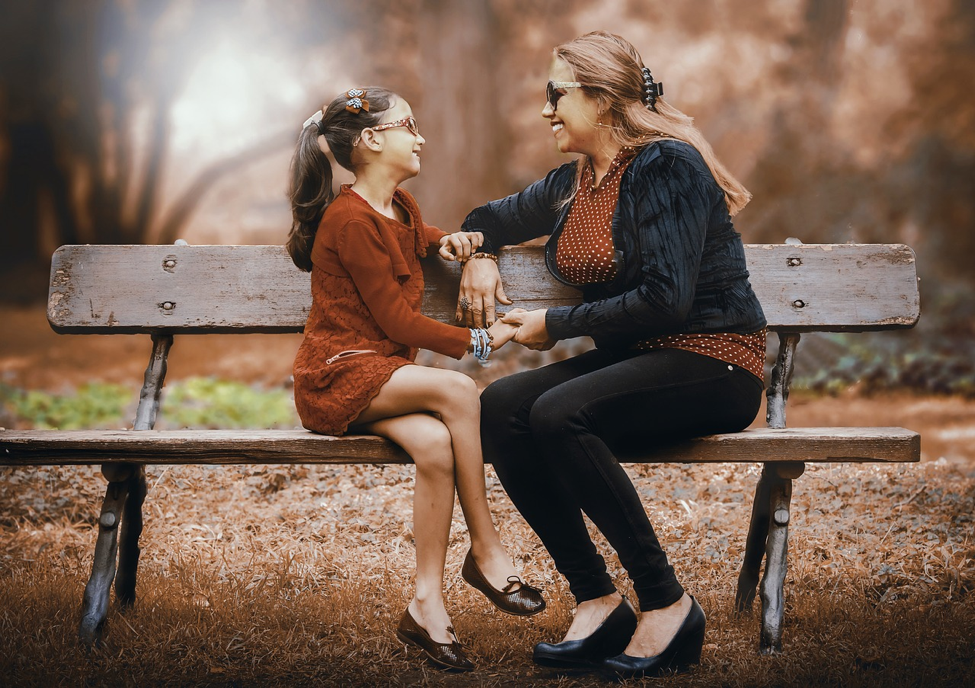 mom and daughter on a park bench